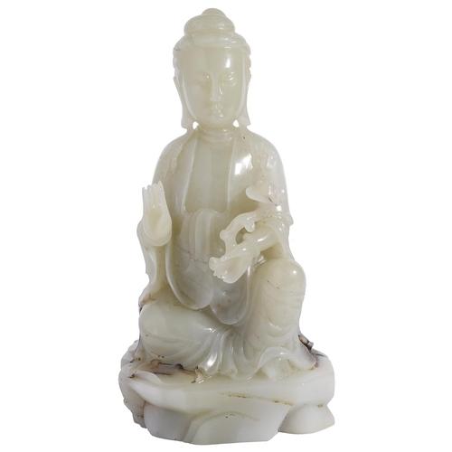 41 - A LARGE CHINESE PALE CELADON JADE FIGURE OF GUANYIN carved kneeling on an oval rockwork base  wearin...