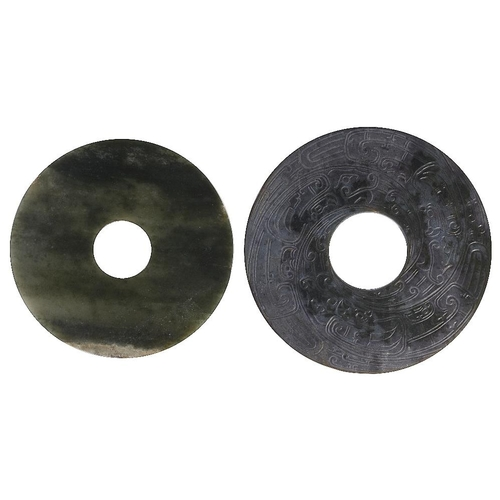 50 - TWO CHINESE ARCHAISTIC JADE BI DISCS the larger carved either side with a stylised dragons  the othe...