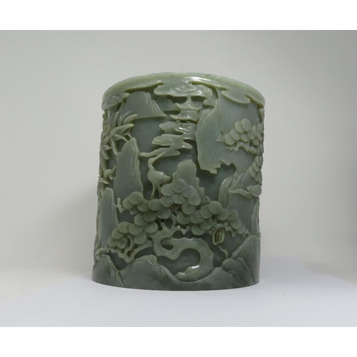 57 - A CHINESE CELADON JADE 'IMMORTALS' BRUSHPOT the cylindrical body deeply carved around the exterior w...