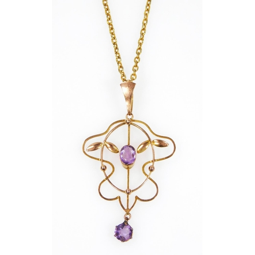 35 - An early 20thC Art Nouveau yellow metal drop pendant, set with two amethyst coloured stones, in a pa...