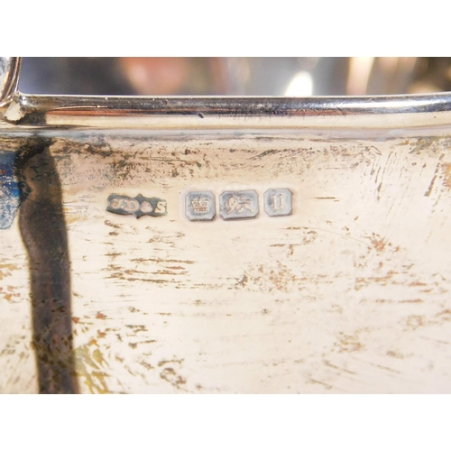 56 - A George V silver cream jug, with shaped spout, C scroll handle, inverted cylindrical stem and circu...