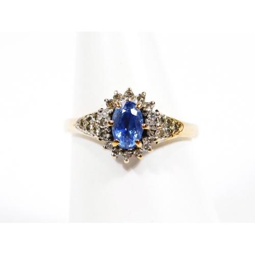 38 - A ladies gold floral set dress ring, with a central blue stone and various white stones, with furthe...