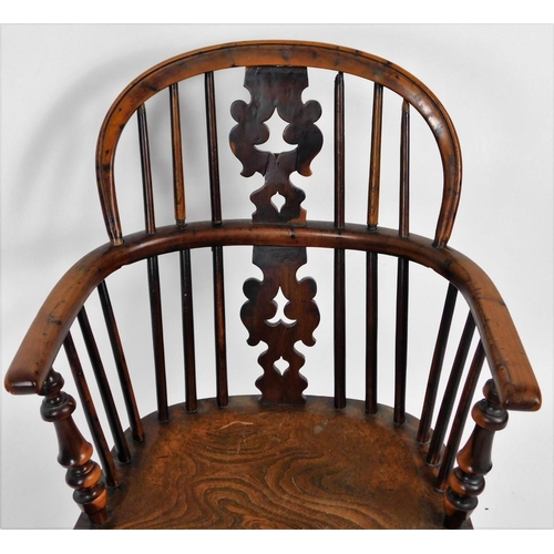 3 - An early 19thC yew wood low back Windsor chair, with pierced Christmas tree splat, turned legs and c...