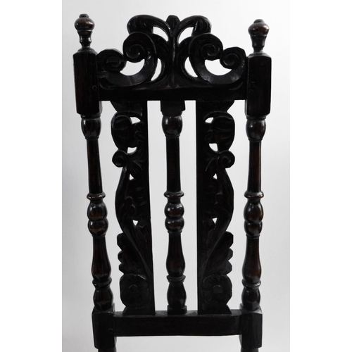 39 - A pair of 17thC oak high back chairs, the back carved with scrolls, etc., on turned supports with so...