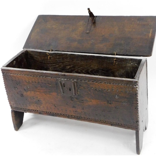 43 - A 17thC small oak boarded chest, the top with shaped edge, the base with a shallow carved frieze and...
