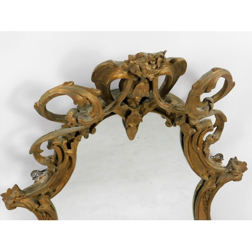 48 - A 19thC gilt gesso wall mirror, the shield shaped frame decorated with scrolls surrounding a central...