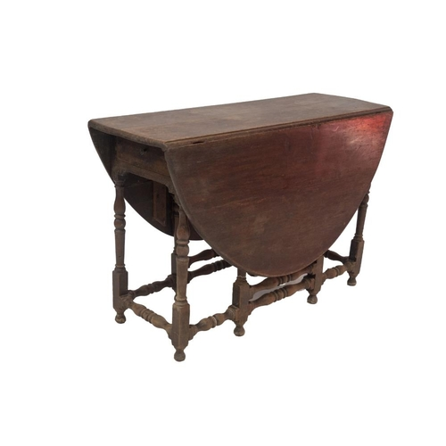 51 - A 17thC walnut gateleg table, with oval drop leaf top, single frieze drawer, baluster turned legs an...