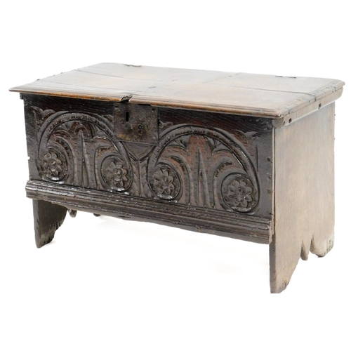 58 - A 17thC oak small boarded chest, with a rectangular top with moulded edge above a frieze carved with...