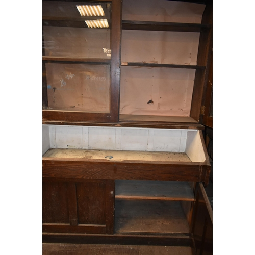163 - An oak school cupboard with glazed doors                    Subject to VAT