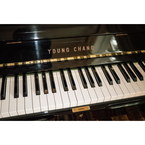 19 - Young Chang (c1987)  A Model U-121 upright piano in a bright ebonised case; together with a duet sto...