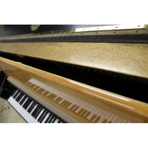 57 - Schimmel (c1957) An upright piano in a modern style maple and ebonised trimmed case....