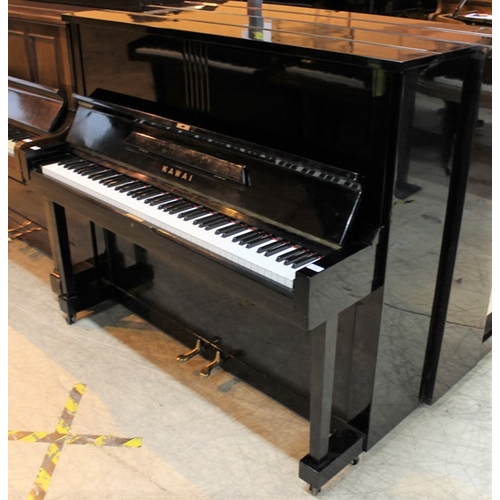 23 - Kawai (c1962)  An upright piano in a traditional style bright ebonised case...