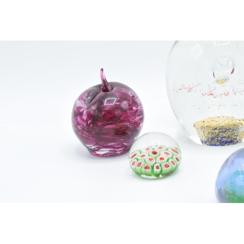 33 - A good collection of glass paperweights to include an apple by  Kerry Glass, a large example and 4 s...