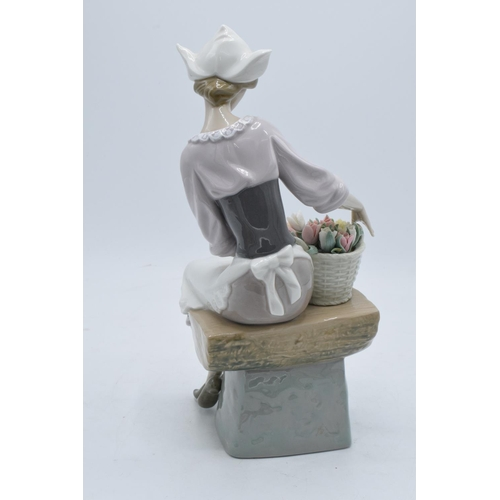 44 - Lladro figurine of a Dutch Girl sat with a basket of flowers. 26cm tall. In good condition with no o...