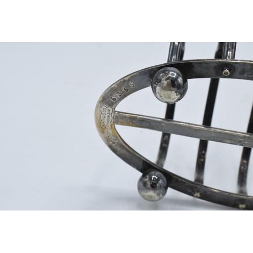 58 - A near pair of silver plated toast racks marked 'Harrods London'. 13cm diameter.