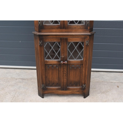 96 - A wooden 20th century Priory style corner display cabinet with glazed upper half. 172cm tall. In goo...