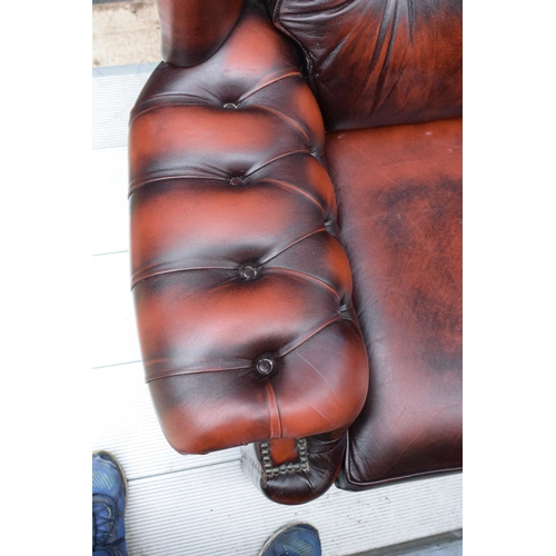 116 - A modern Chesterfield style wingback armchair with button back design raised on 4 wooden feet in oxb...