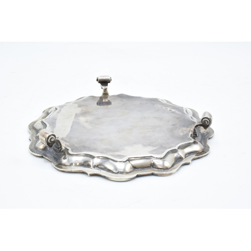 366 - A hallmarked silver salver with shaped edge raised on three feet. Hallmarked for Sheffield 1926. Mad...