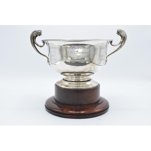381 - A large silver pedestal bowl raised on a turned wooden plinth with ornate handles. Circa 700 grams. ...