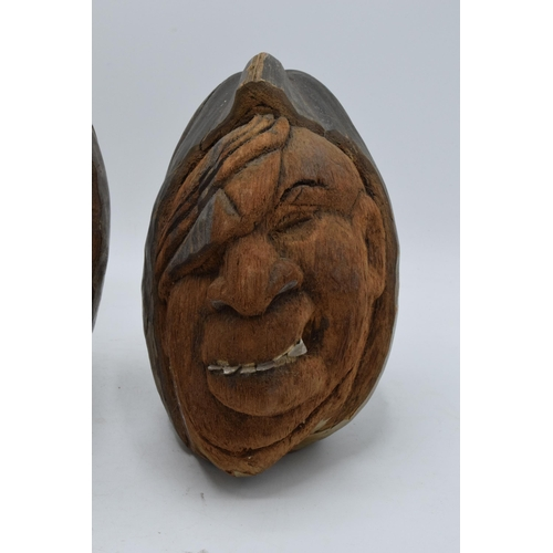 171 - A pair of 20th century carved coconuts or similar in the form of tribal heads (2). Tallest 23cm tall...