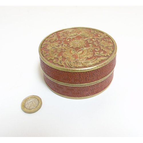 22 - A Chinese burnt orange circular inkstone / pot, the lid decorated with raised gilt relief's of butte...