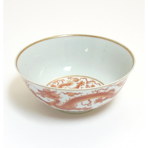 40 - A Chinese iron-red 'Dragon' bowl , depicting two 5 clawed dragons pursuing a flaming pearl across bo...