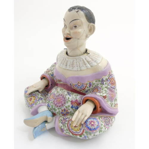 58 - A Schierholz porcelain figure of a Chinese / Oriental man with nodding head and articulate hands, ha...