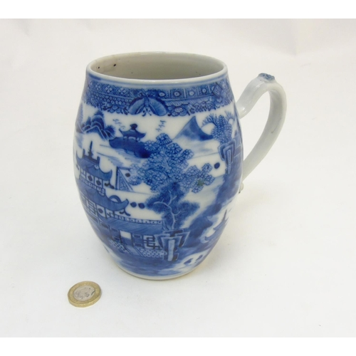 7 - An 18thC Chinese blue and white export tankard, depicting a continuous river and mountainous landsca...