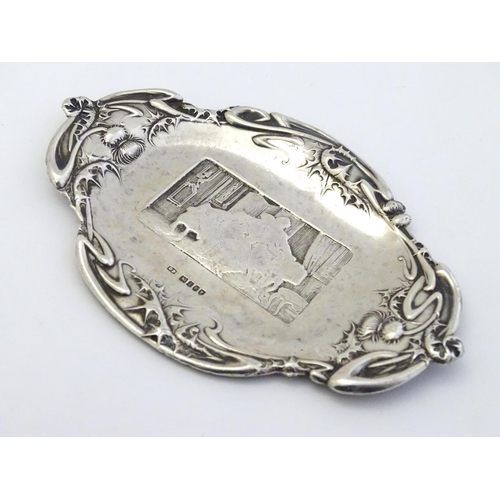 37 - A silver pin dish with thistle decoration to border and interior scene to centre. Hallmarked London ...