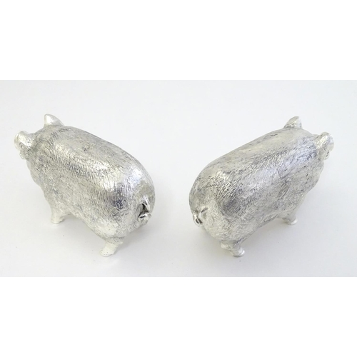 40 - A pair of white metal novelty pepperettes formed as pigs. 2 1/2'' long...