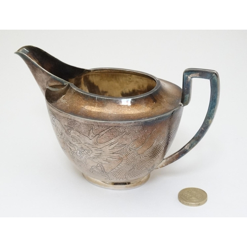 44 - Chinese Export Silver : A silver jug with dragon decoration marked under '  TACKHING 90% SILVER ' an...