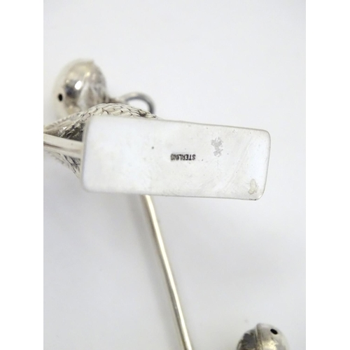 56 - A white metal children's rattle with owl decorations, bells and mother of pearl teether. 5'' long...