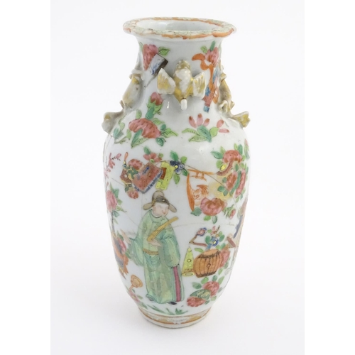 24 - A Chinese Famille Verte rouleau vase with protruding mythical beasts and birds flanking the neck, th...