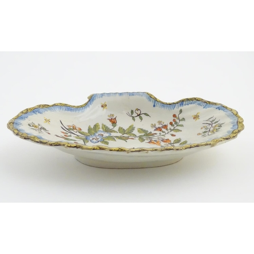 43 - A dish in the form of a shell, decorated with flowers and a bird. Indistinct maker's mark to base. A...