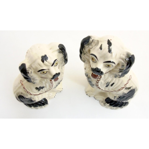 49 - Two Victorian Staffordshire spaniels, with black patch decoration and brown lock and chain, larger o...