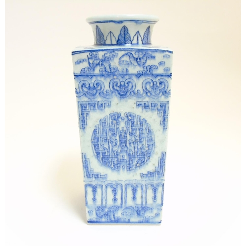 25 - A Chinese blue and white Cong shaped vase, having a tall square tapering body with flared circular n...