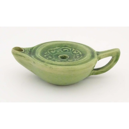58 - A Liberty London green glazed Arts and Crafts pottery oil lamp, decorated with scrolling foliage to ...