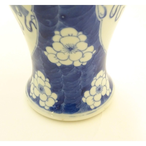 10 - A Chinese, blue and white baluster vase decorated with prunus flowers, the central decoration displa...
