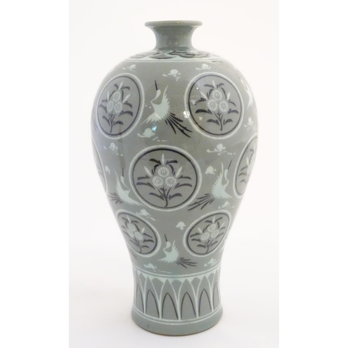 11 - A Korean celadon vase decorated with cranes, clouds and flowers in roundels. Indistinctly marked to ...