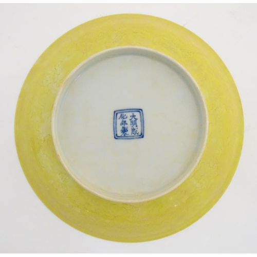 13 - A Chinese yellow bowl decorated with dragons and clouds. Character marks to base. Approx. 8'' diamet...