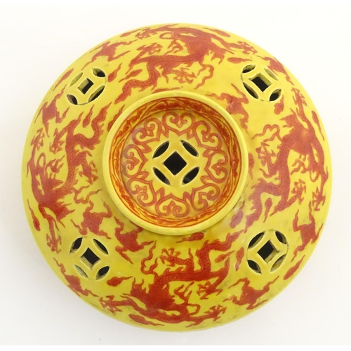 2 - A three-footed Oriental red and yellow circular censer, decorated with dragons and clouds and decora...