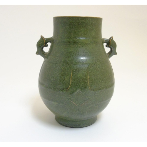 21 - A Chinese tea dust glazed Hu vase, having handles in the form of the tianlu animal, impressed brown ...