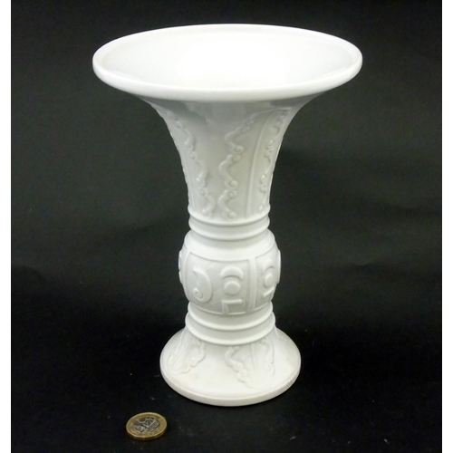 24 - A Chinese white glazed Gu vase of archaic bronze design, having leaves to flared neck / rim and base...