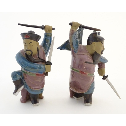 27 - Two Oriental ceramic figures posed in combat with a lustre glaze, each holding two swords, one with ...