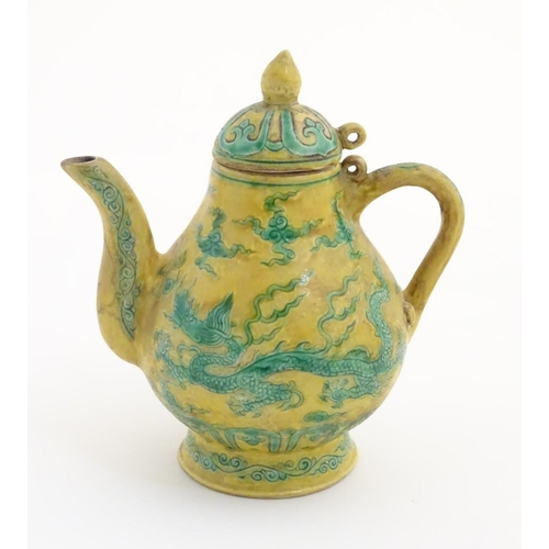 41 - A small Chinese yellow and green teapot decorated with dragons, clouds and scrolling patterns. Chara...