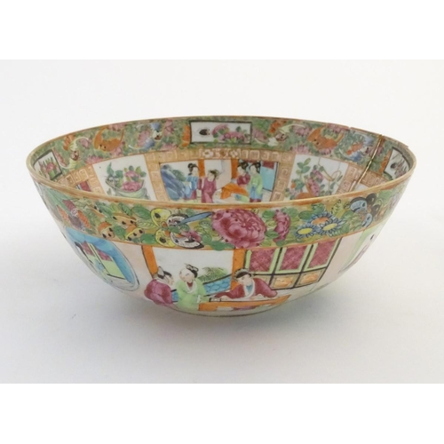 44 - A Cantonese famille rose bowl with panelled decoration depicting figures in traditional dress in var...