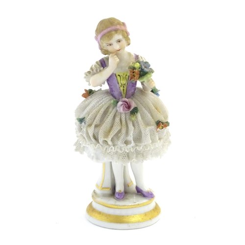 60 - A German porcelain figure of a flower girl with a porcelain lace skirt on a circular base with gilt ...