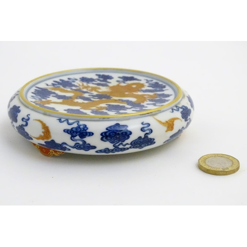 15 - A Chinese decorative stand for a vase/bowl, decorated with a dragon and stylised clouds. Raised on t...