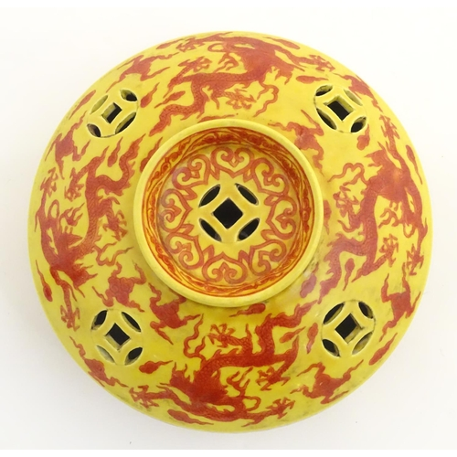 17 - A three-footed Oriental red and yellow circular censer, decorated with dragons and clouds and decora...