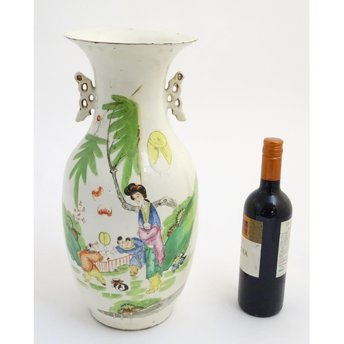 2 - A 20thC Chinese twin handled baluster vase, decorated with figures in a garden with flying lanterns....